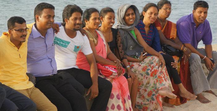 Unga människör som sitter sida vid sida