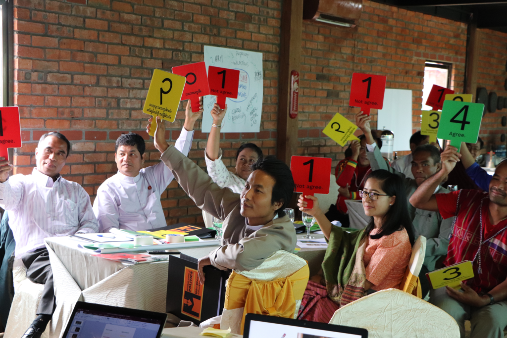 Politicians in a training holding papers with different colors