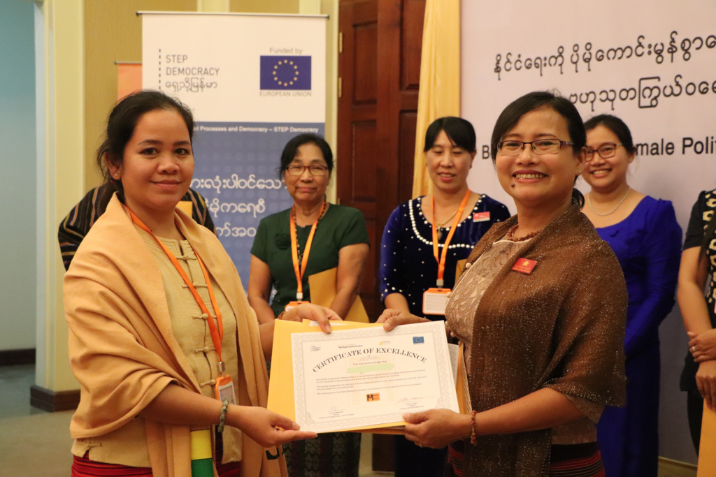 Female politicians in Myanmar showing their training certification